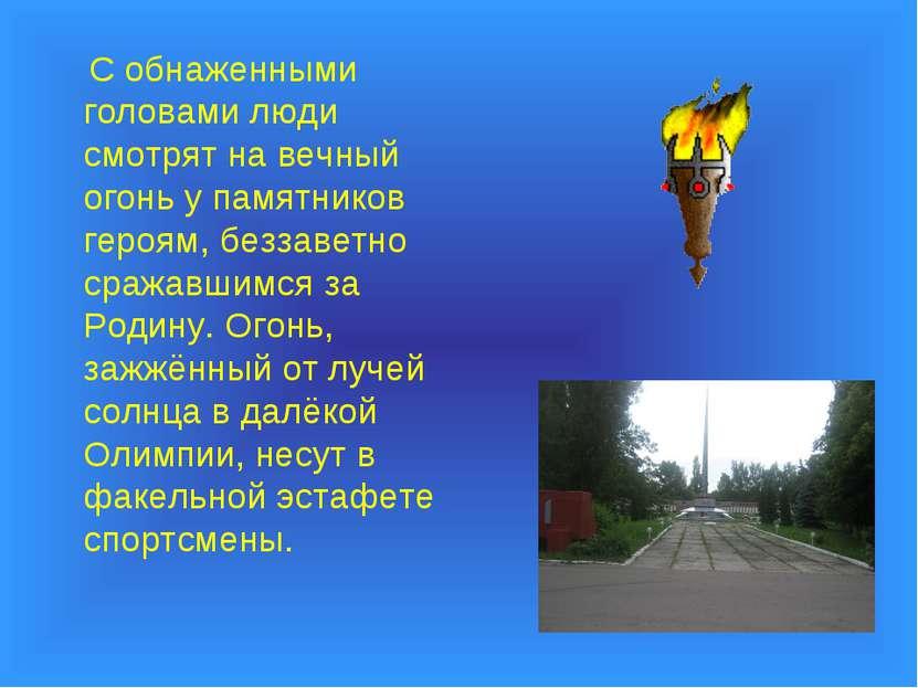С обнаженными головами люди смотрят на вечный огонь у памятников героям, безз...