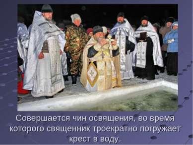Совершается чин освящения, во время которого священник троекратно погружает к...