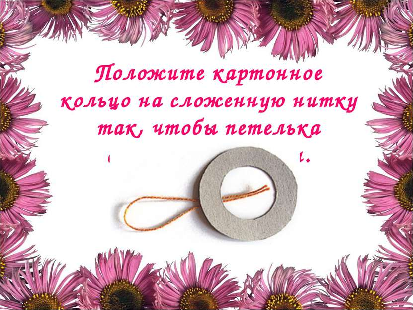 Положите картонное кольцо на сложенную нитку так, чтобы петелька оказалась сн...