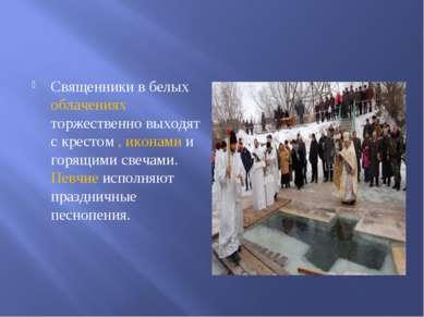 Священники в белых облачениях торжественно выходят с крестом , иконами и горя...